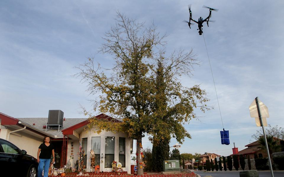A resident watches as a drone delivers a Covid-19 self collection test kit to her home, after being ordered from Walmart, in Texas - Getty Images North America