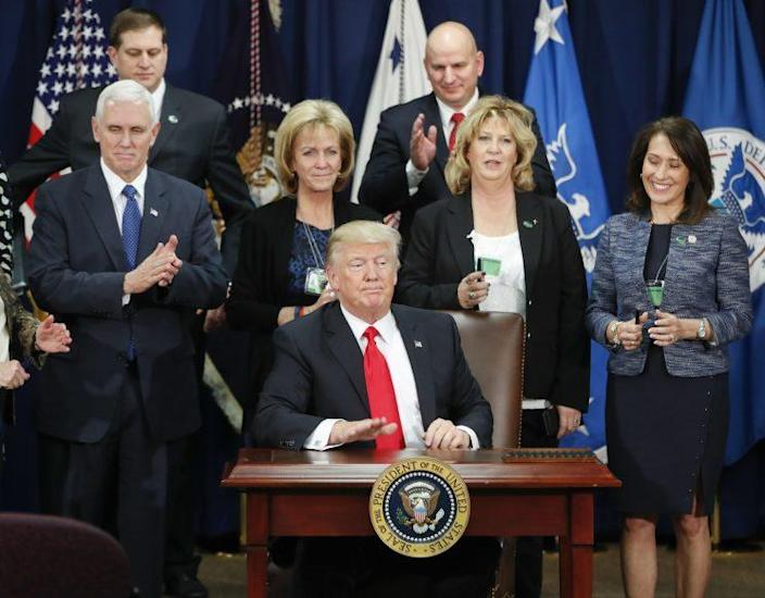 President Trump, accompanied by Vice President Mike Pence and others, taps on the table after signing an executive order for immigration actions to build border wall, Jan. 25, 2017, at the Homeland Security Department in Washington. (AP Photo/Pablo Martinez Monsivais)