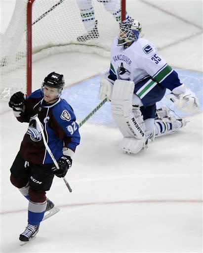 Colorado Avalanche left wing Gabriel Landeskog, left, of Sweden, celebrates a goal against Vancouver Canucks goalie Cory Schneider, right, in the first period of an NHL hockey game on Saturday, April 13, 2013, in Denver. (AP Photo/Chris Schneider)