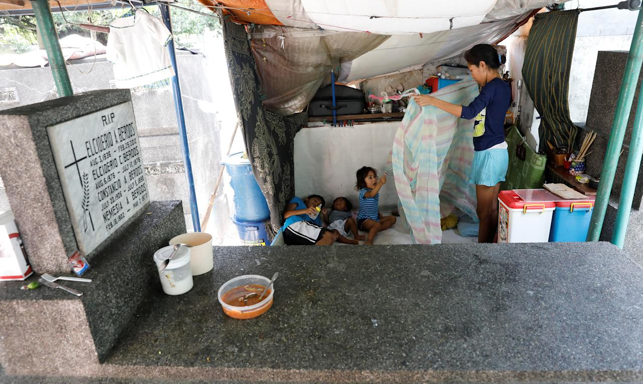 A mother and her children rest at their dwelling inside a cemetery in Makati, Metro Manila in the Philippines May 22, 2017. REUTERS/Erik De Castro