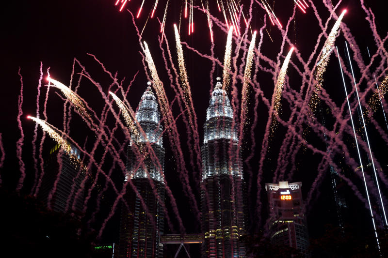 Fireworks explode in front of Malaysia's landmark building, the Petronas Twin Towers, during the New Year's celebration in Kuala Lumpur, Malaysia