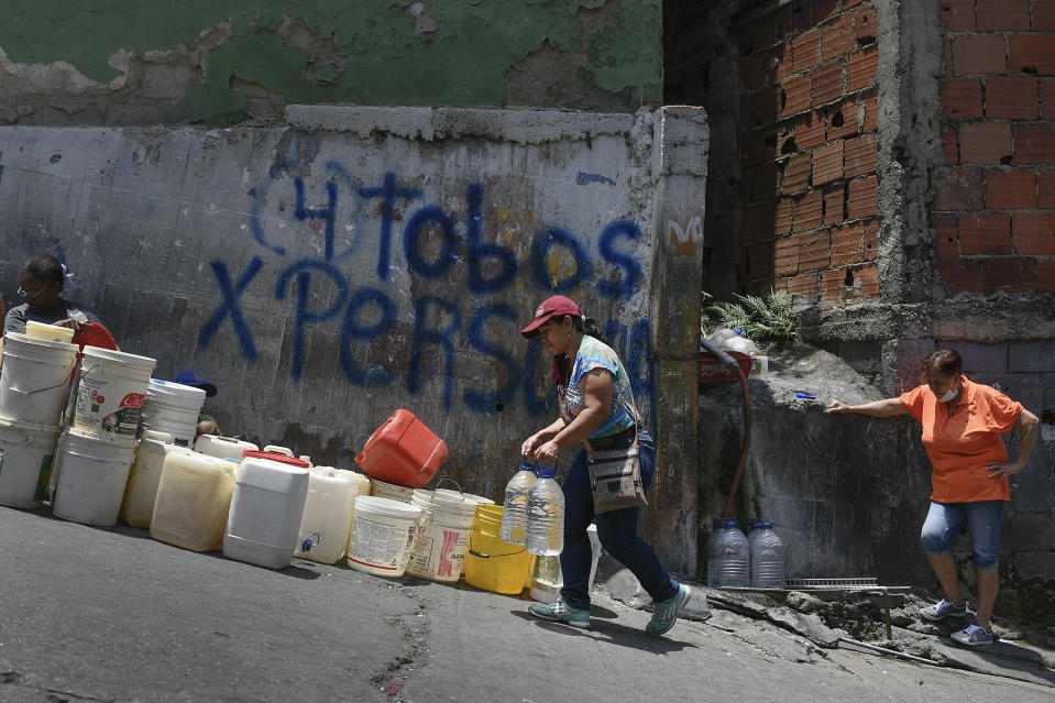 FILE - In this May 9, 2020, file photo, a woman carries containers of water in the Petare neighborhood, one of the poorest slums in Caracas, Venezuela, during a government-imposed quarantine to help stop the spread of the coronavirus. For people around the world who are affected by war and poverty, the simple act of washing hands is a luxury. (AP Photo/Matias Delacroix)