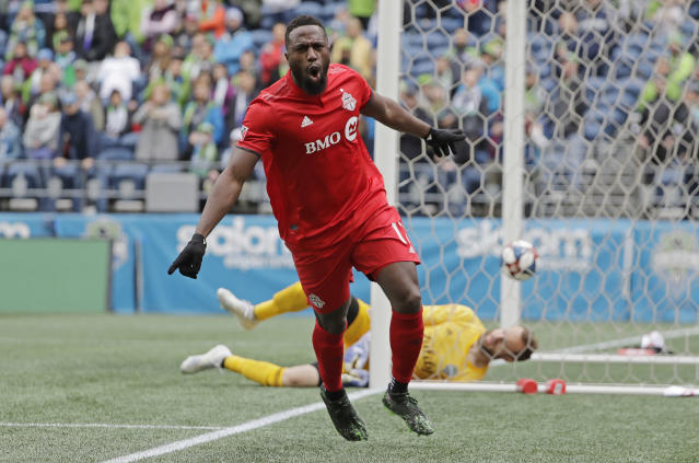 Toronto FC forward Jozy Altidore celebrates after he scored a goal against Seattle Sounders goalkeeper Stefan Frei, right, during the first half of an MLS soccer match, Saturday, April 13, 2019, in Seattle. (AP Photo/Ted S. Warren)