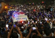 People move with an ambulance carrying casket of Pakistani nuclear scientist Abdul Qadeer Khan following a funeral prayer, in Islamabad, Pakistan on Sunday, Oct. 10, 2021. Khan, a controversial figure known as the father of Pakistan's nuclear bomb, died Sunday of COVID-19 following a lengthy illness, his family said. He was 85. (AP Photo/Anjum Naveed)