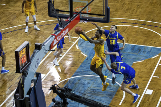 West Virginia Forward Gabe Osabuohien (3) drives for a layup past South Dakota State defenders David Wingett (50) and Baylor Scheierman (3) during an NCAA college basketball game Wednesday, Nov. 25, 2020, in Sioux Falls, S.D. (AP Photo/Josh Jurgens)