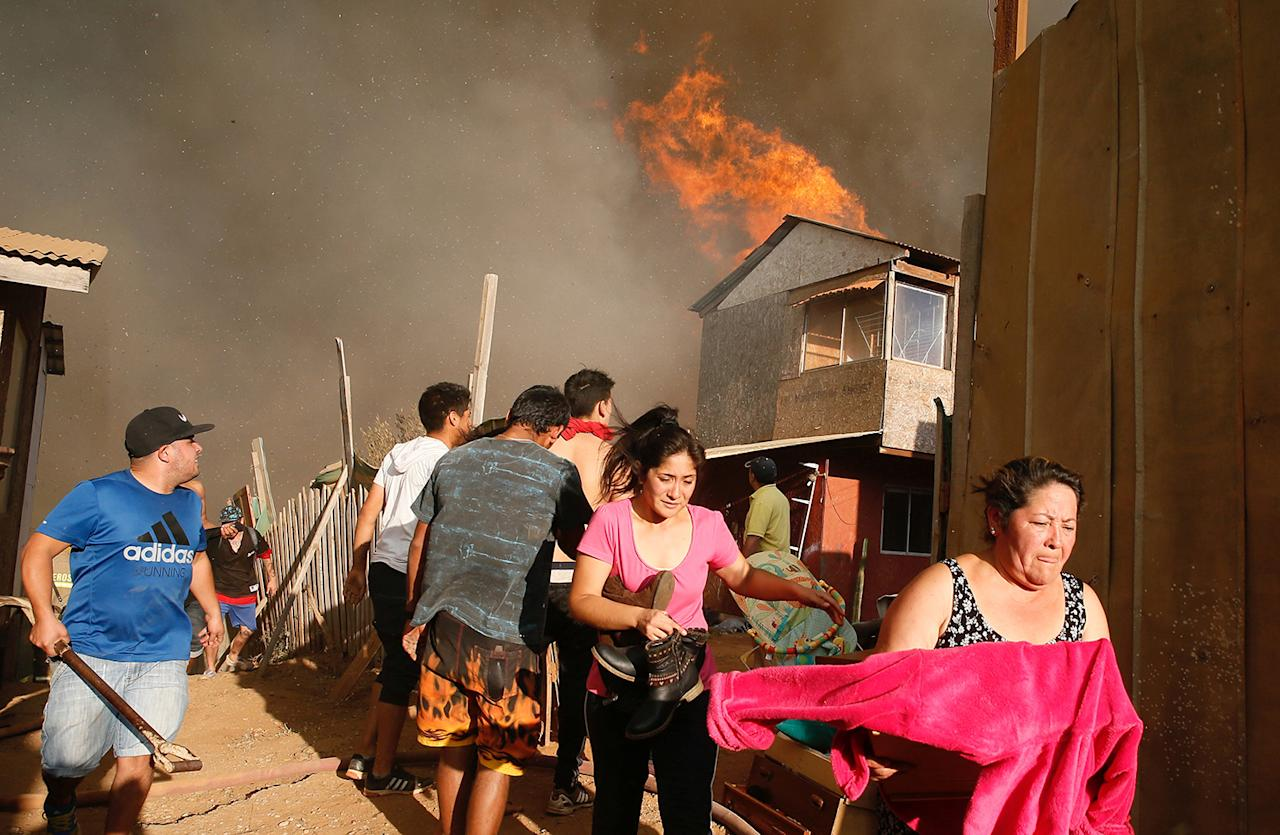 <p>Residents flee with their belongings from a burning house during a wildfire in Vina del Mar, Chile, March 12, 2017. (Photo: Rodrigo Garrido/Reuters) </p>