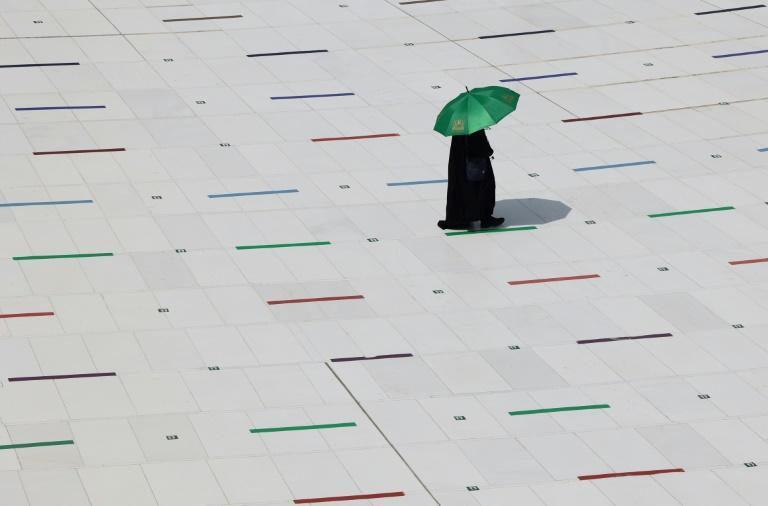 A pilgrim protects herself from the heat at Mecca's Grand Mosque