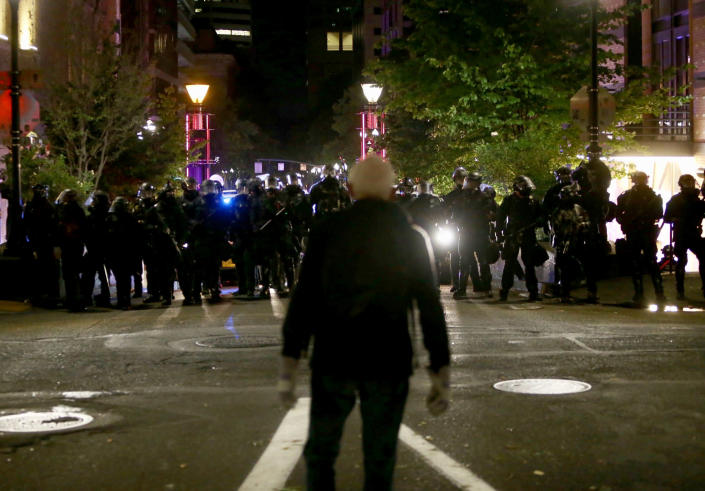 Portland Police and protesters clashed in a demonstration in downtown Portland, early Thursday, Aug. 13, 2020. Officers used tear gas to break up the crowd of several hundred people who gathered near the Mark O. Hatfield U.S. Courthouse, the neighboring Multnomah County Justice Center and a nearby police precinct station. (Sean Meagher/The Oregonian via AP)