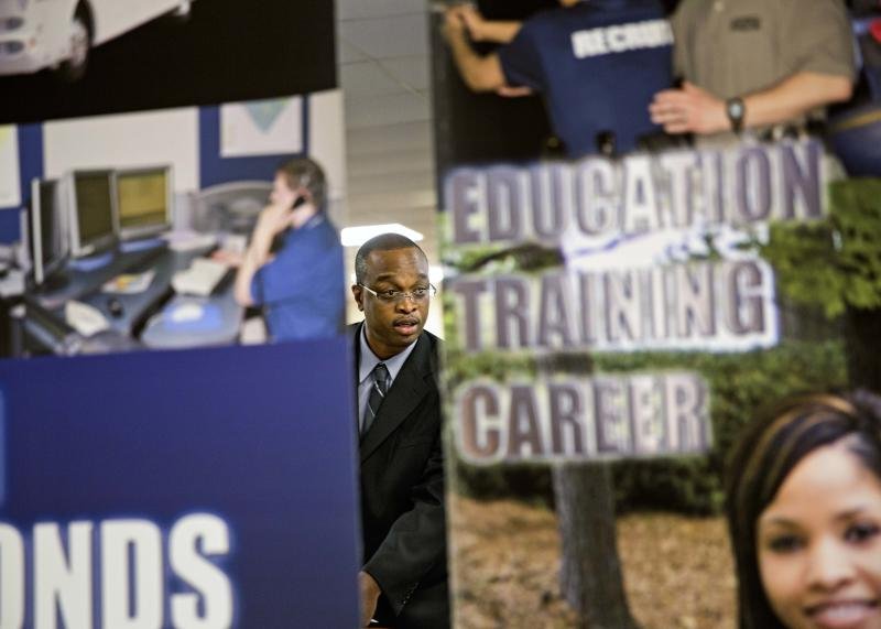 FILE - In this Thursday, Nov. 14, 2013, file photo, employment opportunity banners stand in the foreground as retired U.S. Navy Chief Jerome Porter, of Atlanta, talks with a recruiter during a job fair for veterans at the VFW Post 2681, in Marietta, Ga.  The government reports on job openings and labor turnover for October, on Tuesday, Dec. 10, 2013. (AP Photo/David Goldman, File)