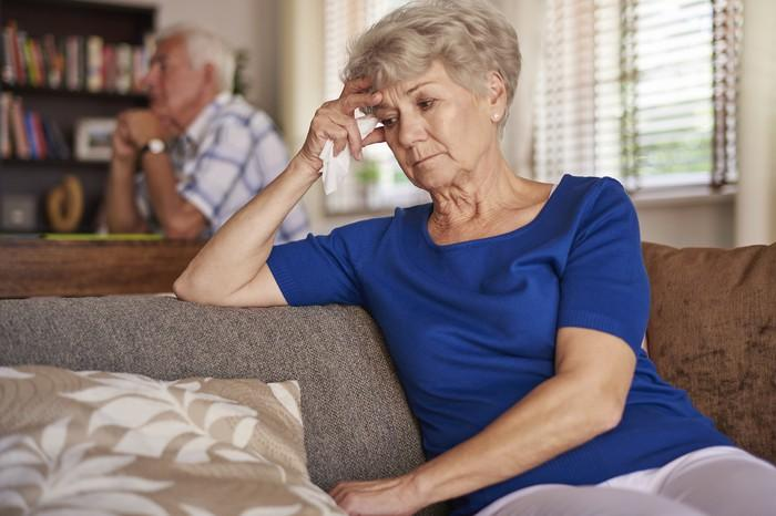 Senior woman sitting on the couch looking worried