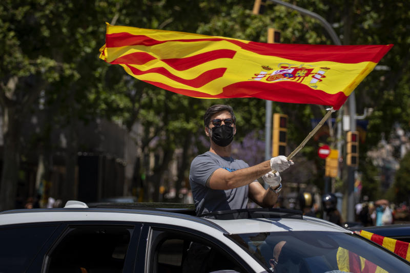 People wave Spanish flags in their cars during a drive-in protest organised by Spain's far-right Vox party against the Spanish government's handling of the nation's coronavirus outbreak in Barcelona, Spain, Saturday, May 23, 2020. Several thousand followers of Spain's far-right Vox party gathered Saturday in their cars and motorbikes in the center of Madrid and other Spanish cities to protest the Spanish government's handling of the nation's coronavirus crisis. (AP Photo/Emilio Morenatti)