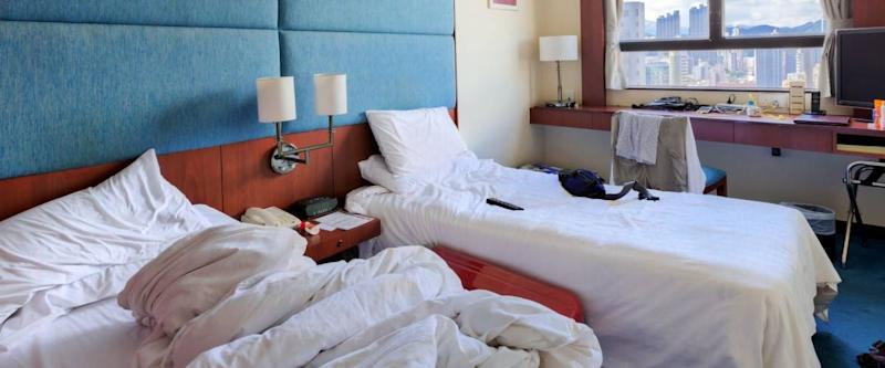 Interior shot of motel room with unmade bed