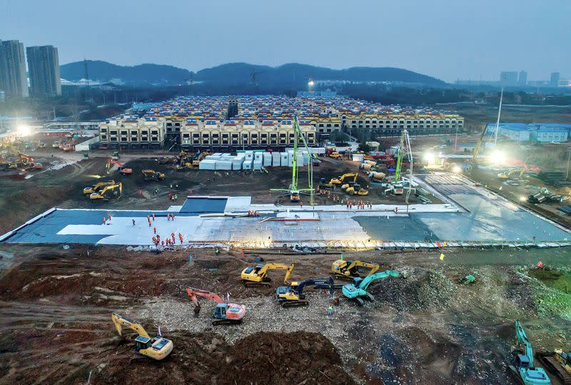 Excavators and workers are seen at the construction site where the new Huoshenshan Hospital is being built to treat patients of a new coronavirus on the outskirts of Wuhan