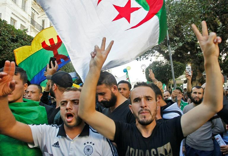 Algerian protesters, with the Berber flag in the background, chant slogans during anti-government demonstrations in the capital Algiers