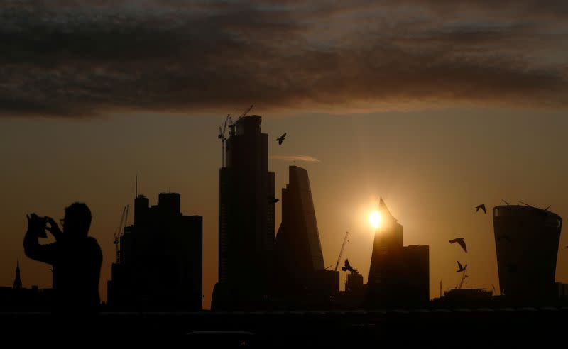 FILE PHOTO: A man takes a photograph of the skyline as the sun rises behind the city of London financial district in London