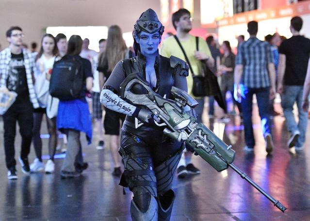 A woman dressed as the fantasy character Widowmaker from the Activision Blizzard videogame Overwatch walks at Gamescom fair in Cologne, Germany, on Aug. 22, 2017. (AP Photo/Martin Meissner)