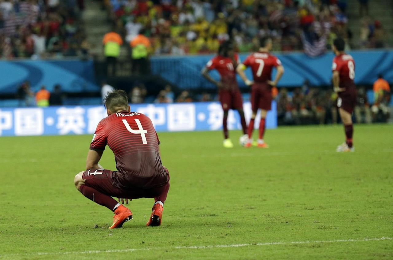 Portugal's Miguel Veloso sits on the ground after United States' Clint Dempsey scored his side's second goal during the group G World Cup soccer match between the USA and Portugal at the Arena da Amazonia in Manaus, Brazil, Sunday, June 22, 2014. (AP Photo/Martin Mejia)