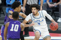 UCLA's Johnny Juzang (3) is defended by Abilene Christian's Coryon Mason, left, and Reggie Miller (10) during the first half of a college basketball game in the second round of the NCAA tournament at Bankers Life Fieldhouse in Indianapolis Monday, March 22, 2021. (AP Photo/Mark Humphrey)