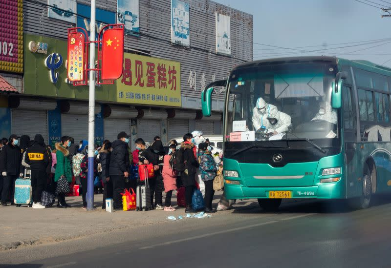 People who are required to undergo centralized quarantine line up to board a bus in Shijiazhuang