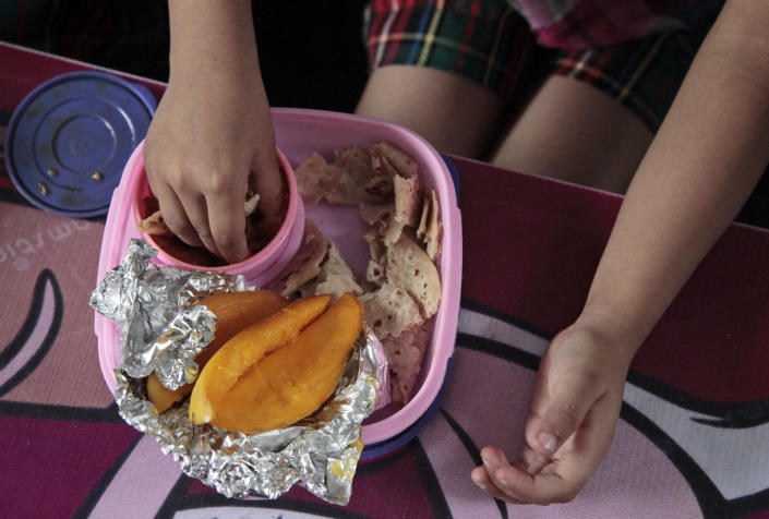 Baani, a 5-year-old Indian schoolgirl, eats her lunch prepared by her mother, consisting of flatbread, a turnip dish and mangoes, at a school in Jammu, India, Tuesday, May 6, 2014. Most countries seem to put a premium on feeding school children a healthy meal at lunchtime. U.S. first lady Michelle Obama is on a mission to make American school lunches healthier too, by replacing greasy pizza and french fries with whole grains, low fat protein, fresh fruit and vegetables. (AP Photo/Channi Anand)