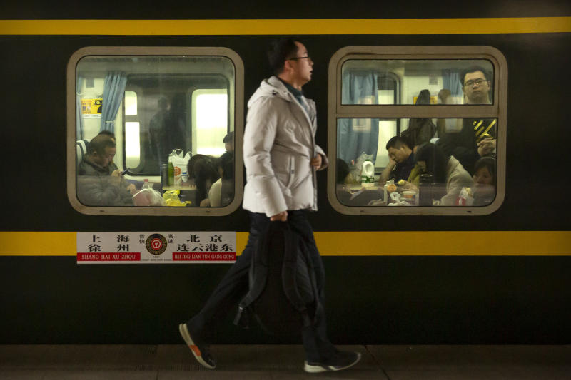 A late-arriving passenger runs to catch his train at the Beijing Railway Station in Beijing, Friday, Jan. 17, 2020. As the Lunar New Year approached, Chinese travelers flocked to train stations and airports Friday to take part in a nationwide ritual: the world's biggest annual human migration. (AP Photo/Mark Schiefelbein)