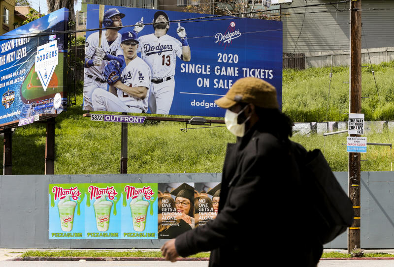 A pedestrian wears a hat and a face mask on Sunset Blvd., in the Echo Park neighborhood of Los Angeles, Thursday, April 2, 2020. Major League Baseball opening day was to have been Thursday, March 26, but was pushed back to mid-May at the earliest because of the coronavirus outbreak. The spring training schedule was cut short on March 12 because on the pandemic, and it remains unclear when and if baseball can resume. (AP Photo/Damian Dovarganes)