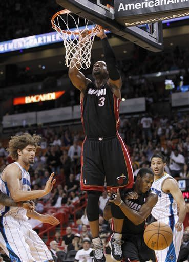 Miami Heat guard Dwyane Wade (3) hangs on the rim after missing a dunk during the first quarter of an preseason NBA basketball game against the New Orleans Hornets, Friday, Oct. 26, 2012 in Miami. AP Photo/Wilfredo Lee)