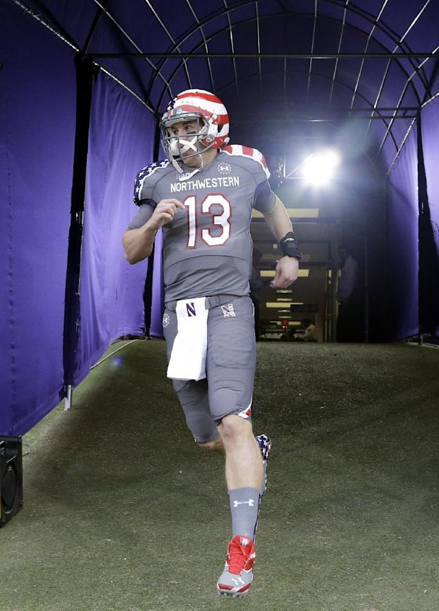 Northwestern quarterback Trevor Siemian (13), wearing the Wildcats new patriotic-themed uniform, runs to the field for an NCAA college football game against Michigan in Evanston, Ill., Saturday, Nov. 16, 2013. (AP Photo/Nam Y. Huh)