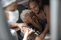 FILE - In this Feb. 1, 2021 file photo, an elderly woman gets a shot of Sinovac COVID-19 vaccine as part of a priority COVID-19 vaccination program for the elderly at a drive-thru vaccination center in Rio de Janeiro, Brazil. Pedro Hallal, an epidemiologist who runs the nation's largest COVID-19 testing program, has calculated that at least 95,000 lives would have been spared had the government not spurned vaccine purchase offers. (AP Photo/Silvia Izquierdo, File)