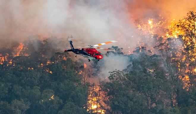 A firefighting helicopter in the East Gippsland region of Victoria. Photo: AAP/ DPA