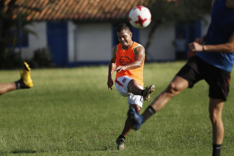 Midfielder Sergio Rojas of Club Sportivo Ameliano of the promotional division, kicks the ball during a training session on his team's pitch, in Asuncion, Paraguay, Friday, Jan. 29, 2021. Because the championship was suspended due to the COVID-19 lockdown, Rojas, 28, a 10-year veteran of the league, now sells eggs and washes cars to survive after not being paid a salary for a year. (AP Photo/Jorge Saenz)