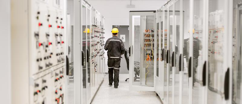 An employee in safety clothing and yellow hard hat walks through a bank of switches in a building's engineering room.