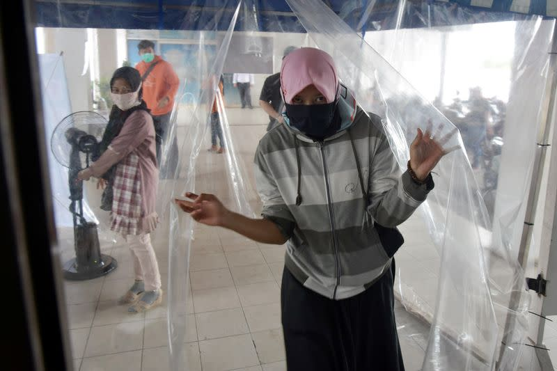 Woman wearing a face mask leaves a disinfection chamber amid the spread of coronavirus disease (COVID-19) outbreak in Pekanbaru
