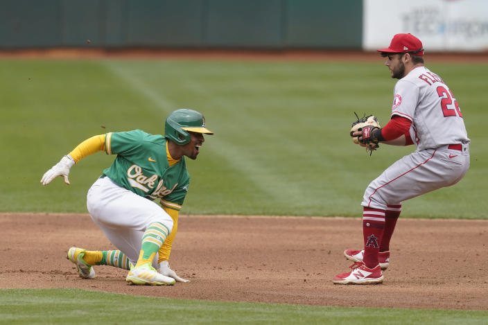 Oakland Athletics' Tony Kemp, left, reacts as Los Angeles Angels shortstop David Fletcher approaches to tag him out during the fourth inning of a baseball game in Oakland, Calif., Saturday, May 29, 2021. (AP Photo/Jeff Chiu)