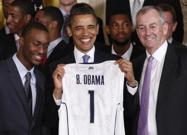 U.S. President Barack Obama is presented with a jersey from Kemba Walker and coach Jim Calhoun at a ceremony honoring the 2011 NCAA men's basketball champions University of Connecticut at the White House in Washington