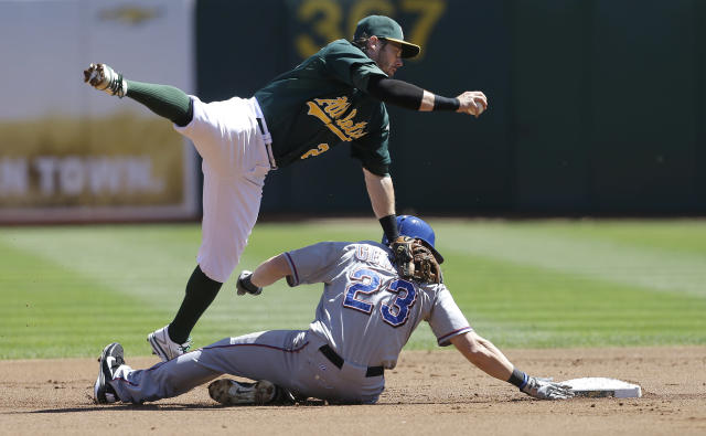 Oakland Athletics second baseman Eric Sogard, top, forces out Texas Rangers' Craig Gentry (23) at second base on a fielder's choice hit into by Ian Kinsler during the first inning of a baseball game in Oakland, Calif., Wednesday, Sept. 4, 2013. (AP Photo/Jeff Chiu)