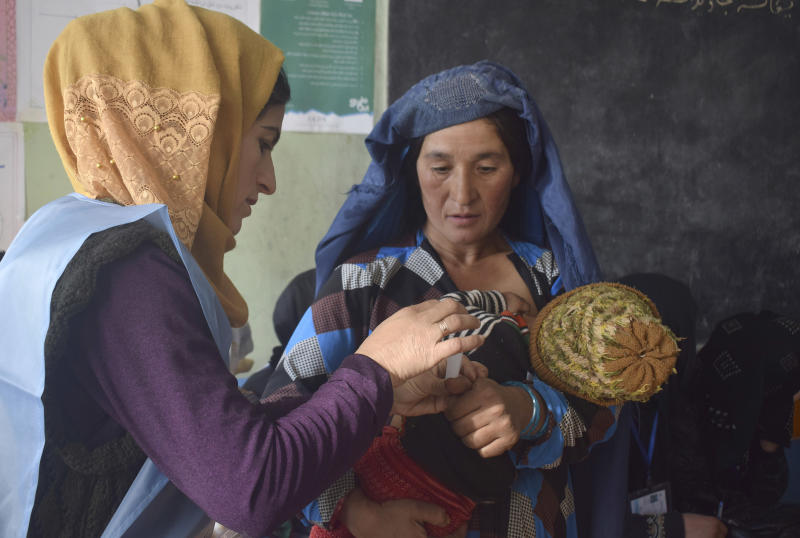 In this Saturday, Oct. 20, 2018, photo, an employee of Independent Elections Commission, left, sticks a biometric sticker on a mother, who is feeding her baby, before casting her vote at a polling station in Faizabad, center of northern Badakhshan province, Afghanistan. Badakhshan province, Afghanistan's parliamentary elections entered a second day on Sunday, Oct. 21, 2018, following violence and chaos that caused delays and interruptions on the first day of polling. (AP Photo/Omer Abrar)