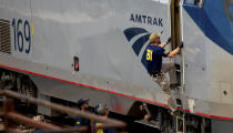 A Federal Bureau of Investigation agent boards an Amtrak train after a shooting aboard the train in downtown Tucson, Ariz., on Monday, Oct. 4, 2021. (Rebecca Sasnett/Arizona Daily Star via AP)