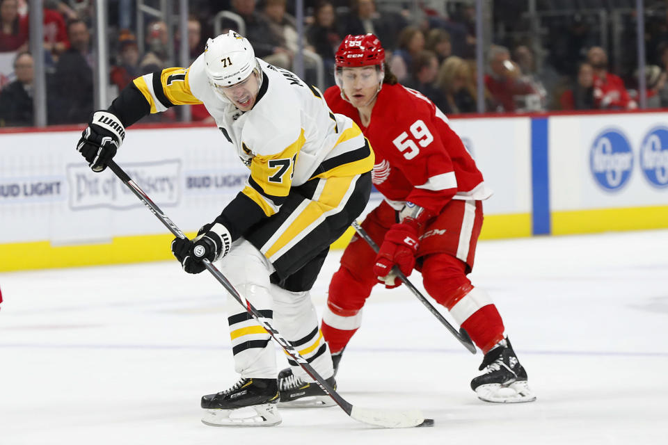 Pittsburgh Penguins center Evgeni Malkin (71) protects the puck from Detroit Red Wings left wing Tyler Bertuzzi (59) in the first period of an NHL hockey game Saturday, Dec. 7, 2019, in Detroit. (AP Photo/Paul Sancya)