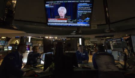Television screen displays Federal Reserve Chair Yellen's news conference as traders work on the floor of the New York Stock Exchange