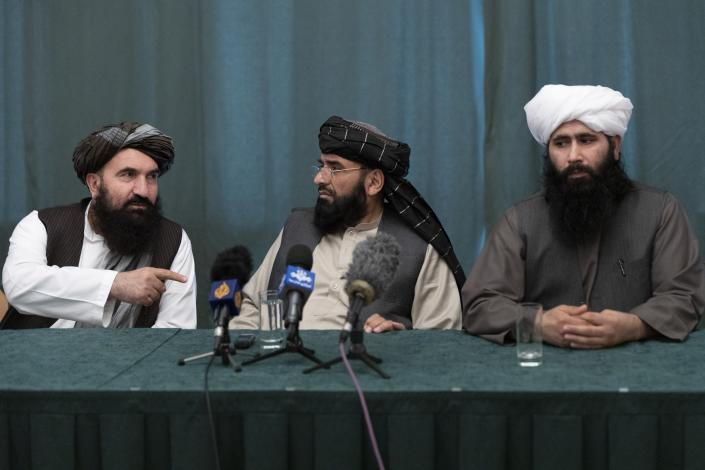 """Members of the Taliban delegation from the left: Khairullah Khairkhwa, former western Herat Governor and one of five Taliban released from the U.S. prison on Guantanamo Bay in exchange for U.S. soldier Bowe Bergdahl, Suhail Shaheen, member of negotiation team, Mohammad Naeem, spokesman for the Taliban's political office attend their joint news conference in Moscow, Russia, Friday, March 19, 2021. The Taliban warned Washington against defying a May 1 deadline for the withdrawal of American and NATO troops from Afghanistan promising a """"reaction"""". (AP Photo/Alexander Zemlianichenko, Pool)"""