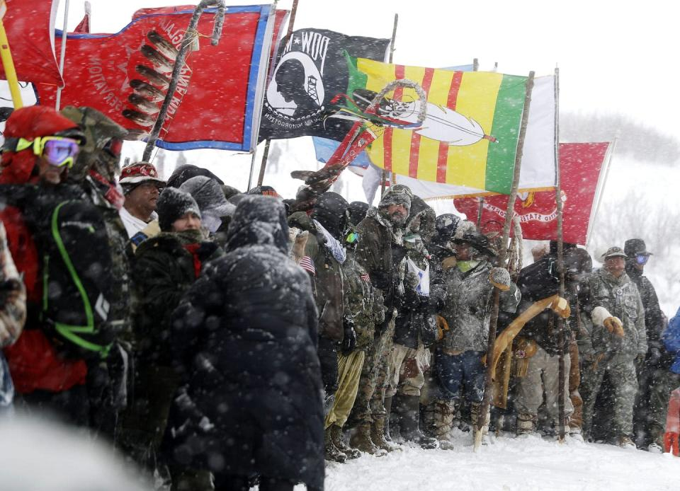 A large group of people gather in the snow holding the flags of Indigenous nations.