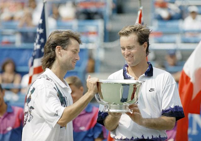 FILE - In this Sept. 10, 1993, file photo, Ken Flach, left, of Alpharetta, Ga., and Rick Leach, right, of Laguna Beach, Calif., check out the winner's trophy after taking the U.S. Open men's doubles title in New York. Flach, who won four Grand Slam titles in men's doubles and two in mixed doubles, died Monday night, March 12, 2018, in California after a brief illness, the ATP World Tour and International Tennis Federation announced Tuesday, March 13, 2018. He was 54. (AP Photo/Elise Amendola, File)