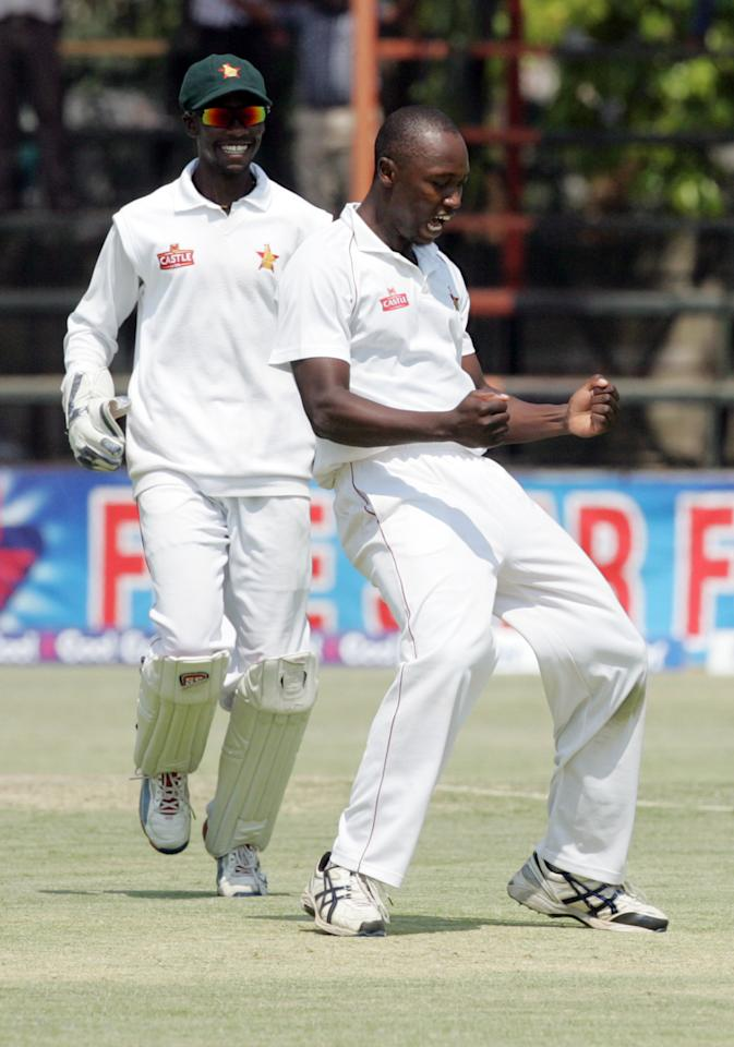 Zimbabwe bowler Tendai Chatara (R) celebrates a wicket with teammate Richmond Mutumbami (L) on September 14, 2013 during the fifth day of the second test match between Pakistan and hosts Zimbabwe at the Harare Sports Club.                                                             AFP PHOTO / JEKESAI NJIKIZANA        (Photo credit should read JEKESAI NJIKIZANA/AFP/Getty Images)