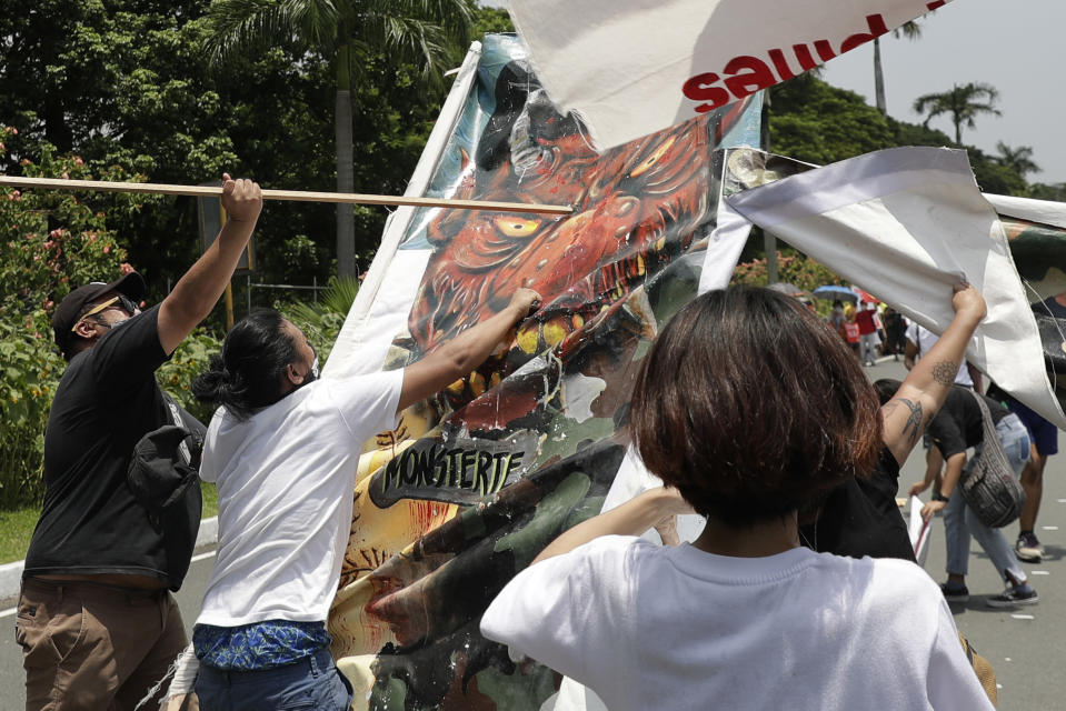 Protesters hit a caricature of Philippine President Rodrigo Duterte as they hold a rally in time for his State of the Nation Address on Monday, July 27, 2020 in Manila, Philippines. Hundreds of protesters marched, staged motorcades and held a rally against a new anti-terror law and other issues Monday in the Philippine capital despite police threats of arrests ahead of the president's annual state of the nation speech. (AP Photo/Aaron Favila)