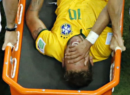 Brazil's Neymar grimaces in pain as he is carried off pitch on a stretcher during their 2014 World Cup quarter-final match against Colombia in Fortaleza