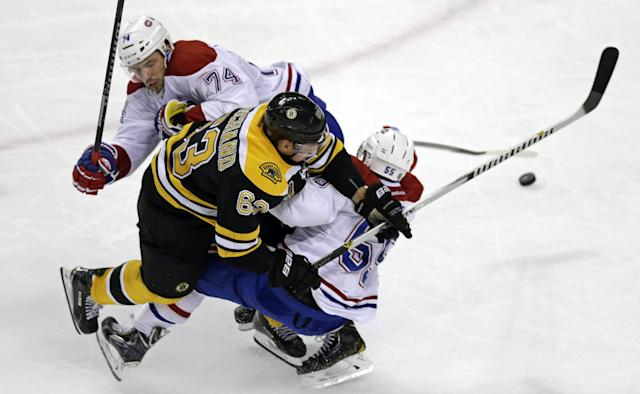 Boston Bruins left wing Brad Marchand (63) tries to thread between Montreal Canadiens defensemen Francis Bouillon (55) and Alexei Emelin (74) during the third period of Game 1 in the second-round of the Stanley Cup playoff series in Boston, Thursday, May 1, 2014. (AP Photo/Charles Krupa)