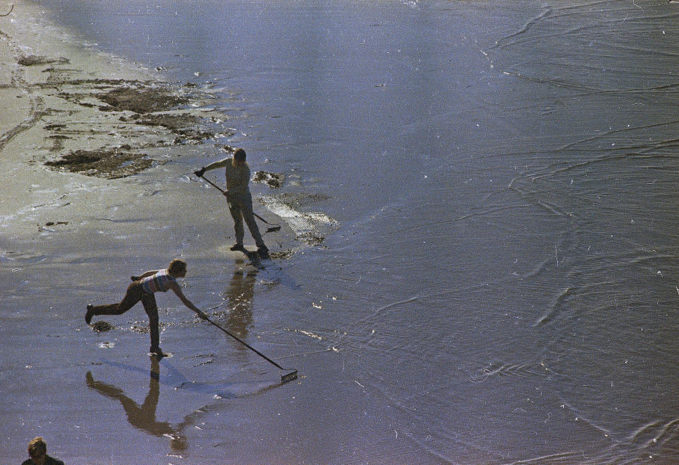 FILE - In this Feb. 7, 1969, file photo, workmen using pitchforks, rakes and shovels attempt to clean up oil-soaked straw from the beach at Santa Barbara, Calif. The oil spill more than a generation ago helped give rise to the modern environmental movement itself. (AP Photo/File)