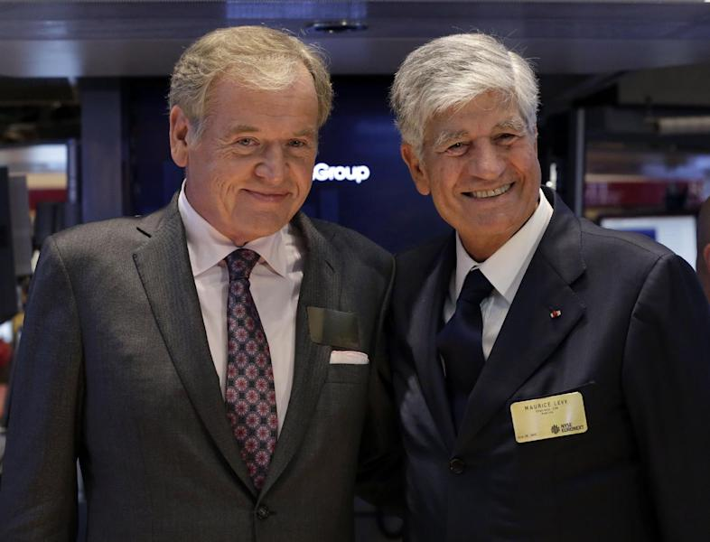 """FILE - This July 29, 2013, file photo shows Omnicom Group President and CEO John Wren, left, and Publicis Groupe Chairman and CEO Maurice Levy pose for photos on the floor of the New York Stock Exchange in New York City. The CEO of Publicis Groupe, Maurice Levy, says the planned deal with Omnicom to create the world's largest advertising firm collapsed over unresolvable differences over how to implement a """"merger of equals."""" The merger announced in July was intended to help the firms counter the growing clout of Internet giants such as Facebook and Google, which can bypass advertising companies altogether, as well as strengthen growth in Asia and Latin America. (AP Photo/Richard Drew, File)"""