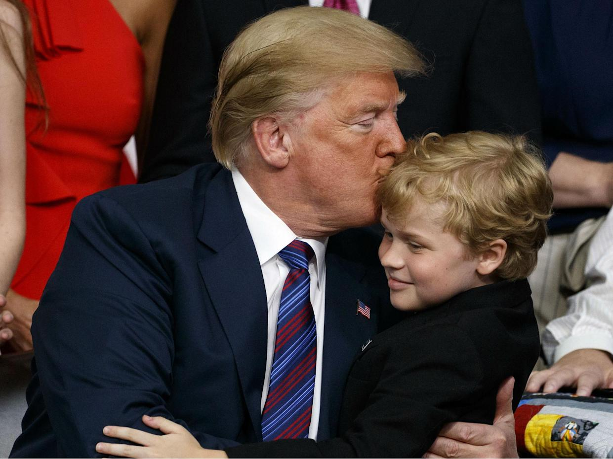 Mr Trump embraces a child with muscular dystrophy after signing the right to try law: AP